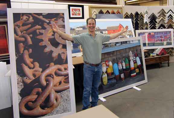 Curt standing in front of four large picture frames